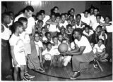 Image for Roy Campanella (standing left), Dodger catcher, and Jackie Robinson (right foreground), Dodger infielder, explain the fine points of basketball to members of the Harlem, New York YMCA. The two men started jobs as physical directors at the YMCA on Nove...